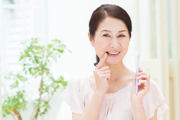 歯に指を当てているシニア女性